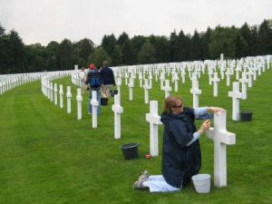 "Dr. Duncan's Mother polishing the graves of U.S. soldiers from the Battle of the Bulge. ""We have gone forth from our shores repeatedly over the last hundred years and we've done this as recently as the last year in Afghanistan and put wonderful young men and women at risk, many of whom have lost their lives, and we have asked for nothing except enough ground to bury them in, and otherwise we have returned home to seek our own, you know, to seek our own lives in peace, to live our own lives in peace. But there comes a time when soft power or talking with evil will not work where, unfortunately, hard power is the only thing that works."" - Colin Powell"